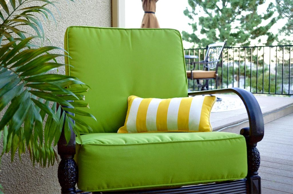 green patio cushion with yellow and white striped pillow